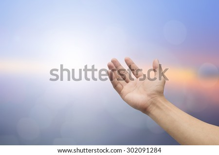 Human hands open palm gesture on blurred sea background: hand receiving power form god.religious concept.