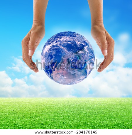 Human hands protect global Earth over gas clouds and Sun over green glass a World Environment Day Concept Elements of this image furnished by NASA
