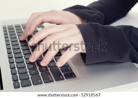 Human hands typing on a laptop
