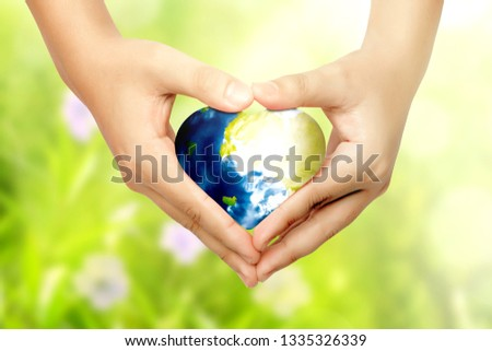 Human hands with heart shapes holding earth planet with heart shapes over green background. Earth hour concept #1335326339