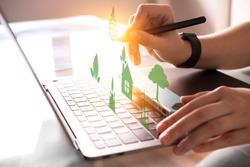 Human Hands working with ecology system icons on grey Laptop in office backdrop, sunlight effect. Freelance worker. Eco friendly, environmental awareness, ecological safety concept. Smart working