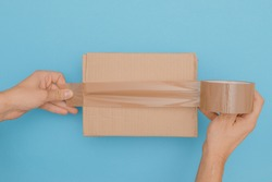 human hands wrap up a cardboard box with parcel tape