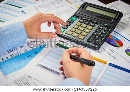 human hands write balance sheet summary on a background balances sheets with calculator #1143359225
