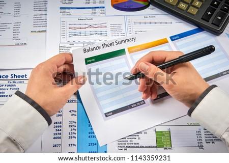 human hands write balance sheet summary on a background balances sheets with calculator #1143359231