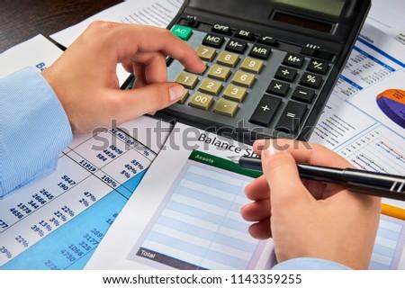 human hands write balance sheet summary on a background balances sheets with calculator #1143359255