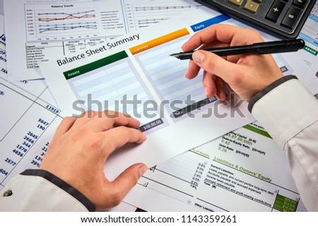 human hands write balance sheet summary on a background balances sheets with calculator #1143359261