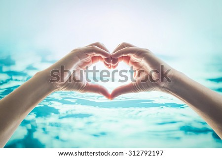 Human happy hands in heart shape showing love and friendship on blurred wavy clean blue turquoise color water background: Saving world water and natural environment and ocean concept/ campaign/ idea
