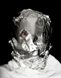 human head is wrapped with aluminium foil. only the right eye is looking throug a hole in the foil, black background