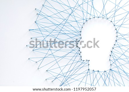 Human head shape made from a large grid of pins connected with string. Communication technology and mental health concept