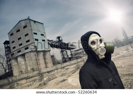 Human in gas mask outdoors and industrial factory on a background