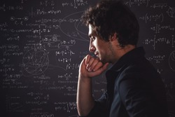 Human intellect. Training and research, concept. Pensive man and physical and mathematical formulas on the background
