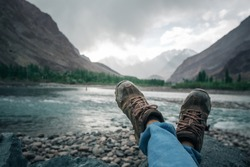 Human leg wearing shoe for hiking mountain relaxation.