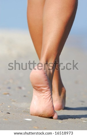 Human legs. Beautiful woman walking on the beach