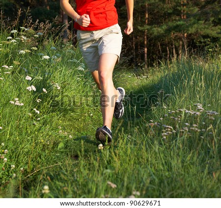 Human legs running in the green field