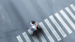 Human life in Social distance. Aerial top view with blur man with smartphone walking at pedestrian crosswalk on grey pavement street road with empty space.