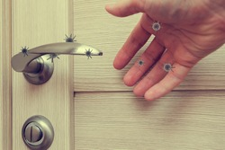 human life through which germs and viruses spread, door handle in an apartment in a room or house with hand and finger, the concept of germs sitting on the door handle