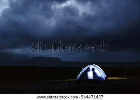 Human outlines in tent on stormy night