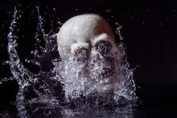Human plastic skull falling in water isolated on black background.