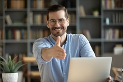 Human resource agent male recruiter sit at desk extends his hand to camera for handshake greeting applicant showing polite gesture start job interview in modern office. Welcoming, cooperation concept