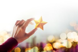 Human Resource Management or Talent Concept, Hand holding and Raise up a Golden Star, Blurred Bokeh Light as background