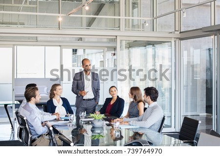 Human resource manager training people about company and future prospects. Group of businesspeople sitting in meeting room and listening to the speaker. Leader man and work group in a conference room.