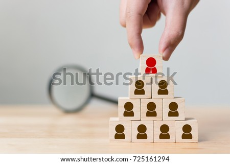 Human resources management and recruitment business concept, Hand putting wood cube block on top pyramid and magnifying glass, Copy space