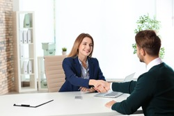 Human resources manager shaking hands with applicant before job interview in office