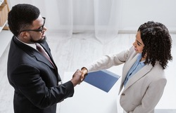 Human resources manager shaking hands with successful vacancy applicant at office, above view. Headhunting specialist welcoming new employee into company team. Career fair concept