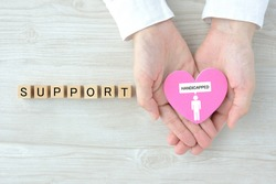 Human's hand covering heart object with handicapped person pictogram