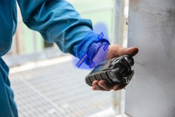 Human's hand holding the Portable Gas Detector for detect combustible gas , flammable gas , toxic gas and oxygen depletion in a confined spaces before starting work.