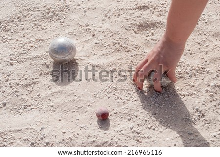 Human\'s hand taking a petanque ball on the ground