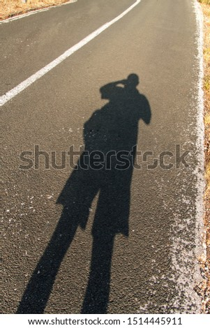 Human shadow on the road. Shadow of a man on asphalt in the morning sun. Sunrise on the road. Shadow of man.