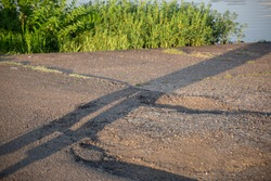 Human shadow stretching toward the corner of asphalt where green space meets water