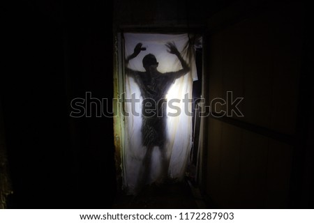 Human silhouette behind packing film in dark creepy room of abandoned building.