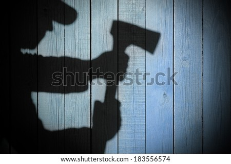 Human Silhouette with Axe in shadow on wooden background, with space for text or image. #183556574