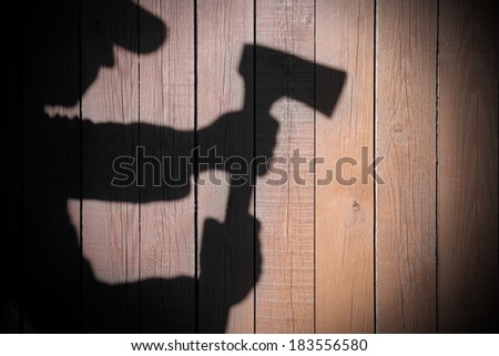 Human Silhouette with Axe in shadow on wooden background, with space for text or image. #183556580