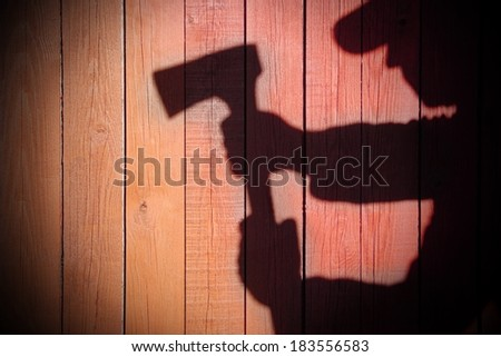 Human Silhouette with Axe in shadow on wooden background, with space for text or image. #183556583