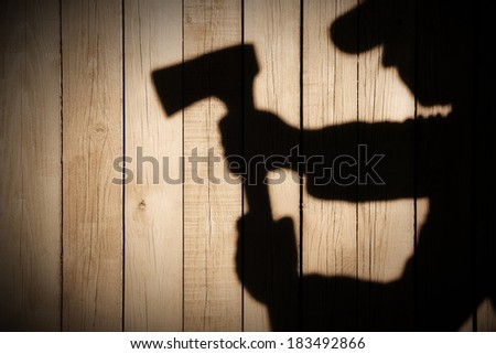 Human Silhouette with Axe in shadow on wooden background, with space for text or image. You can see more silhouettes and shadows on my page.  #183492866