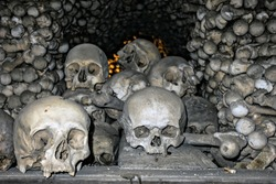 Human Skeleton bones and skulls background. Abstract concept Skeleton grave. Part of interior decorated marble skull and bones church wall hell.