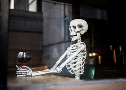 Human skeleton bones sat in leather chair in pub holding a glass of alcohol wine waiting a long time for pubs and bars to re-open after being closed during Covid-19 coronavirus pandemic lockdown