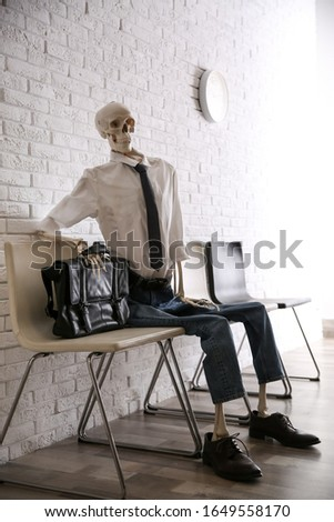 Human skeleton in office wear sitting on chair near brick wall indoors