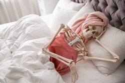 Human skeleton in silk pajamas and towel lying on bed indoors