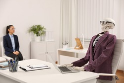 Human skeleton in suit using laptop at table and woman waiting on chair in office