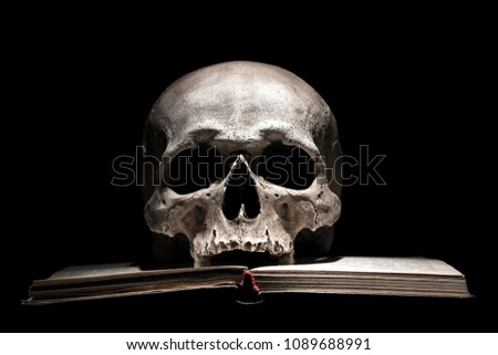 Human skull on old open book on black background. Dramatic concept. #1089688991