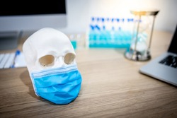 Human skull or cranium head wearing blue surgical mask with test tube set and computerl in medical laboratory. Coronavirus (COVID-19) infection prevention and vaccination.