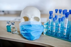 Human skull or cranium head wearing blue surgical mask with test tube set and vaccine vial in medical laboratory. Coronavirus (COVID-19) infection prevention and vaccination.