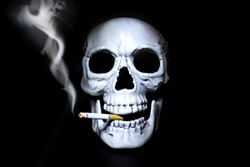 Human skull with a smoking cigarette in his mouth on a black background. Symbol of the dangers of smoking.