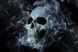Human skull with smoke on dark background