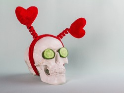 Human skull with two red hearts and cucumber on a background with copy space. Healthy Valentine's day alone.