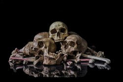 Human skulls and pile of bones are laid on the mirror with a reflection on a night where the atmosphere is scary and dim  lights isolate on a black background. Life and death concept. Still life image
